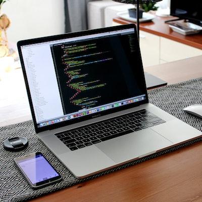 photo of a mac computer with web development markup